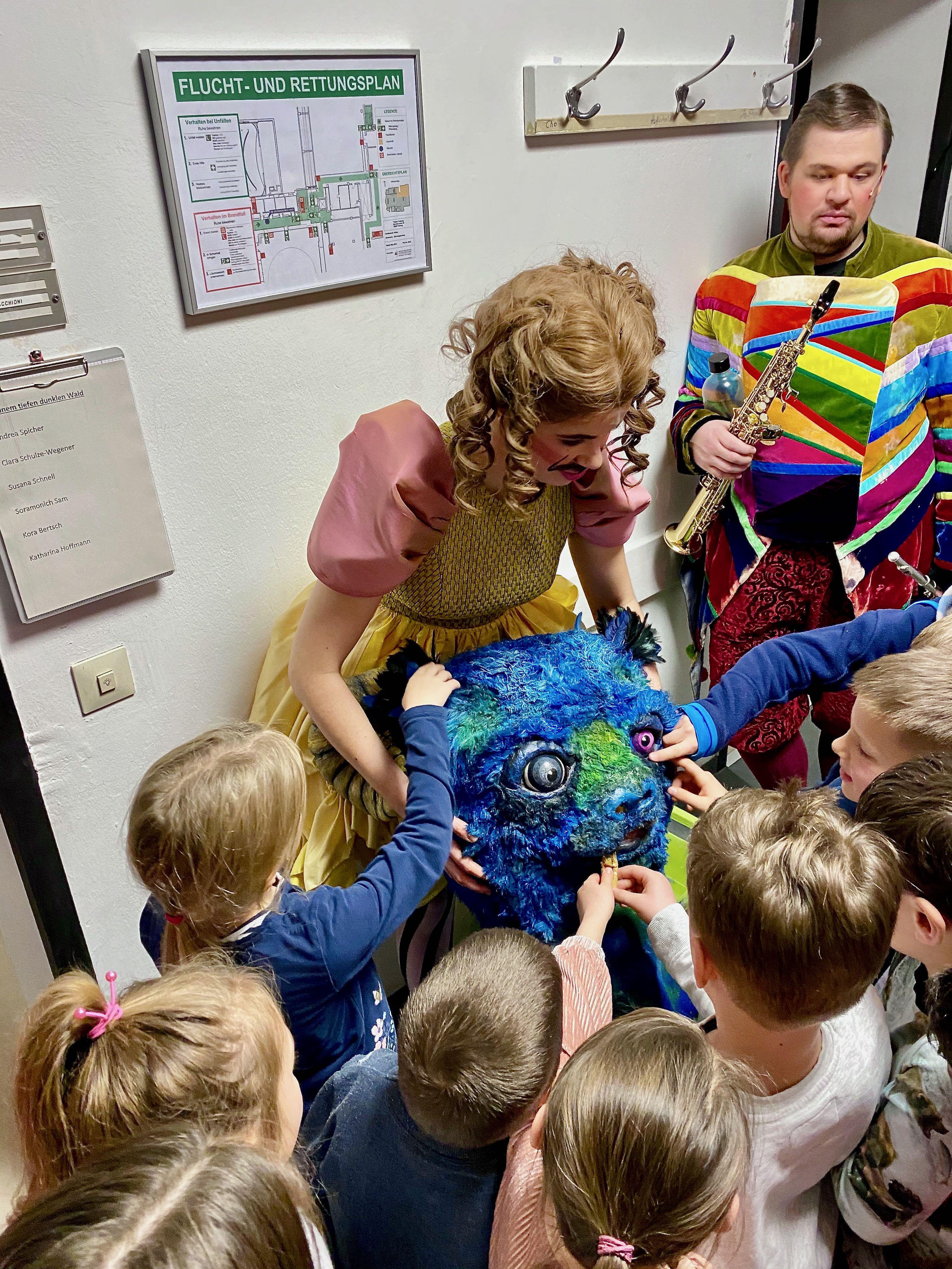 Andrea Spicher zeigt den Kindern die Maske des Untiers